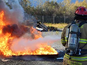 A firefighter practices on live fire in a controlled situation during the 2013 Marine Firefighting Symposium. Photo by Alan Sorum.