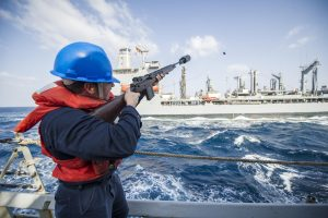 Photo shows Coast Guard officer firing a messenger shot line from one Coast Guard vessel to another. This is one method of connecting tow lines between a tug and a tanker.