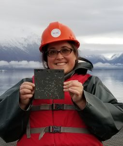 Photo of staff member holding a settling plate from a visual monitoring trip.