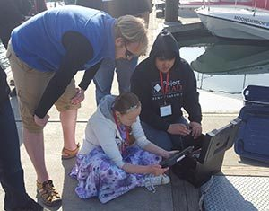 Instructor Axel Gillam leads students to investigate marine invertebrates in the Homer harbor.