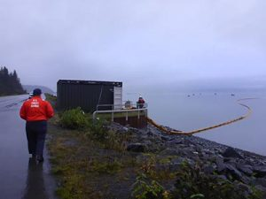 Coast Guard personnel oversee the deployment of boom to protect the Solomon Gulch fish hatchery.