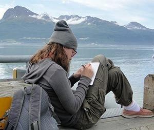 Copper River Stewardship Expeditioner writes a journal entry. Valdez Marine Terminal in the background.