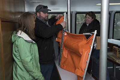 Roy Robertson, the council's drill monitor, shows Alaska SeaLife Center staff how oil spill boom functions using a small sample section.