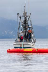 A fishing vessel pulls oil spill boom during a recent drill.