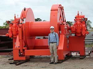 Council volunteer Jim Herbert stands next to large winches waiting to be installed on a tug headed for Alaska.