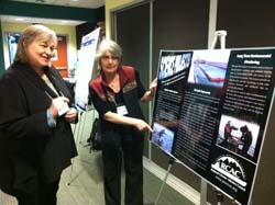 At a 2012 conference, Linda shows a poster about the council's science projects to Sue Saupe, Director of Science and Research at Cook Inlet Regional Citizens' Advisory Council.