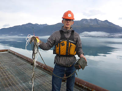 Council staffer Austin Love collects a settlement plate from the Alyeska terminal. Alyeska hosted plates to gather samples from that location. Photo by Nelli Vanderburg.