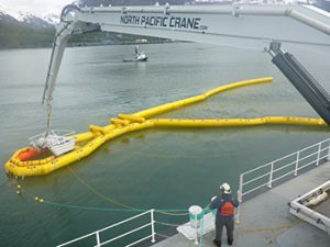 The new Crucial skimmers, pictured here being lowered into a new Current Buster oil collection boom during a barge deployment, are more efficient at collecting spilled oil.