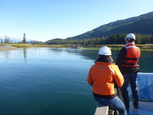 Photo of representatives from the Alaska Department of Environmental Conservations and SERVS monitoring as as responders from the fishing vessel fleet deploy boom in Golden Bay, northwest Prince William Sound.